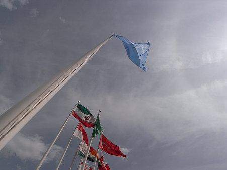 晴れ渡る空にたなびく国連の旗と各国の国旗