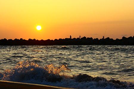 日本海に沈む夕陽と釣り人