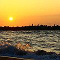 写真: 日本海に沈む夕陽と釣り人