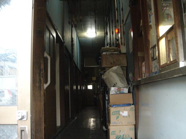 トトロハウス入口 右側の小窓がフロント。年季の入った廊下、左側におっそろしく古い扉が並ぶ。DSC01635